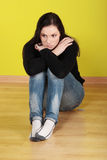 A worried and afraid young woman. Sitting on the flor Royalty Free Stock Photos