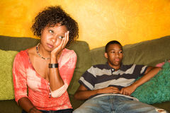 Worried African-American woman sitting with teen. Worried woman sitting on couch with teen boy Royalty Free Stock Image