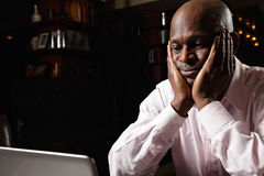 Worried african guy at laptop Royalty Free Stock Photography