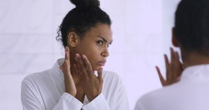 Worried african lady upset with dry skin looking in mirror