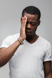 Worried afroamerican guy feels sad and troubled. Troubled, thoughtful african american man with closed eyes suffering. Sadness, worrying, headache, migraine stock photo