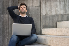 Worried or alleviated young man with laptop Stock Image