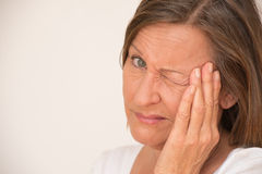 Worried angry upset woman one eye closed Stock Photography