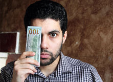 Worried arab young businessman with dollar bills money. Arab young muslim business man feeling confused and worried with dollar bills on one of his eye Royalty Free Stock Photo