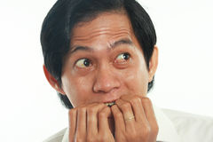 Worried Asian Businessman in Scared Gesture. Photo image portrait of a funny young Asian businessman looked very scared and worried, close up portrait, biting stock photography