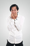 Worried Asian Businessman in Scared Gesture. Photo image portrait of a funny young Asian businessman looked very scared and worried, half body close up portrait royalty free stock images