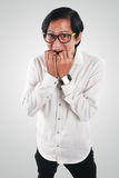 Worried Asian Businessman in Scared Gesture. Photo image portrait of a funny young Asian businessman looked very scared and worried, half body close up portrait royalty free stock photography