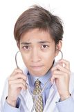 Worried Asian doctor portrait. Close up portrait of young Chinese doctor with stethoscope with a worried frowning emotional expression as if communicating a bad Royalty Free Stock Photos