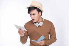 Worried asian male tourist holding passport over grey background Stock Photos