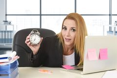 Worried attractive blond business woman holding alarm clock sitting at office desk working with computer laptop stock photo