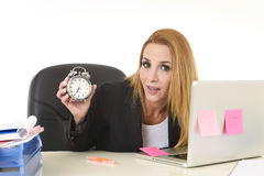 Worried attractive blond businesswoman holding alarm clock sitting at office desk working on laptop Royalty Free Stock Photo
