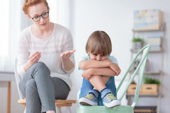 Worried autistic boy and psychiatrist Stock Photos