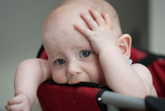 Worried Baby Holding Head. A young baby girl holds her head with her hand as she sits with a concerned look on her face. Her blue eyes stare directly at the Royalty Free Stock Images