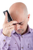 Worried bald  man with cellphone. Worried bald man looking down with a cellphone supported in the forehead. Lilac shirt. Isolated Stock Photos