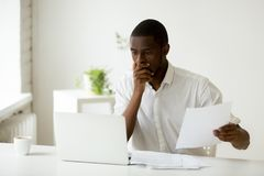 Worried black worker witnessing laptop operation failure. Frightened worried African American worker made a mistake desperately looking at laptop screen Stock Photography