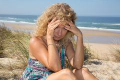 Worried blond girl on the beach sitting on the sand Stock Image