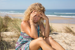 Worried blond girl on the beach sitting on the sand Royalty Free Stock Image
