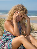 Worried blond girl on the beach sitting on the sand Stock Images