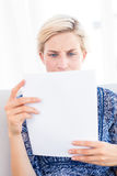 Worried blonde woman reading a paper. In the living room royalty free stock photos