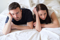 Worried and bored lovers couple after a fight lying in bed stock image