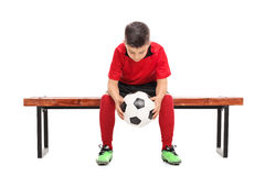 Worried boy in football shirt sitting on a bench Stock Photography