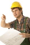 Worried builder with floor plan. Worried builder holding floor plan, pointing to some problem. Isolated on white stock photography