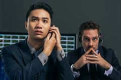Worried business brokers. Two worried business brokers looking at the electronic stock exchange board Royalty Free Stock Photos