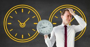 Worried business man holding a clock against background with clocks. Digital composite of Worried business man holding a clock against background with clocks Stock Photos