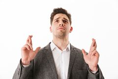 Worried business man in jacket praying with crossed fingers. While looking up over white background Royalty Free Stock Photo