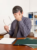 Worried Business Man Rubbing Tired Eyes. Man at his desk in an office setting, rubbing his tired eyes, worrying, exhausted, surrounded by paperwork stock images