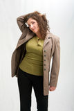 Worried business woman. Dressed in a green shirt, black pants and brown blazer, grabbing her hair up, isolated Stock Images