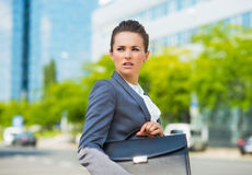Worried business woman with briefcase in modern office district Royalty Free Stock Image