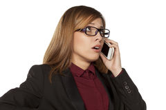 Worried business woman. With eyeglasses talking on her smartphone Stock Photography