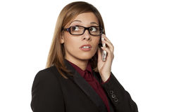 Worried business woman. With eyeglasses talking on her smartphone Royalty Free Stock Photography