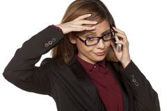 Worried business woman. With eyeglasses talking on her smartphone Stock Images