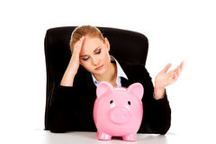 Worried business woman with a piggybank behind the desk Stock Image