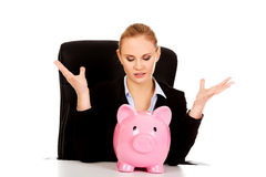 Worried business woman with a piggybank behind the desk.  Stock Images