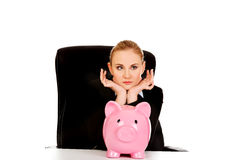 Worried business woman with a piggybank behind the desk.  Royalty Free Stock Photos