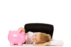 Worried business woman with a piggybank behind the desk.  Stock Photo