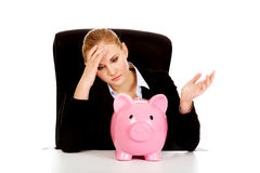 Worried business woman with a piggybank behind the desk.  Royalty Free Stock Photography