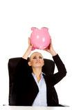Worried business woman with a piggybank behind the desk.  Royalty Free Stock Images