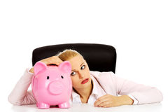 Worried business woman with a piggybank behind the desk.  Stock Photography