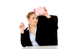 Worried business woman with a piggybank behind the desk.  Stock Image