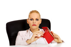 Worried business woman sitting behind the desk with empty wallet Stock Photo