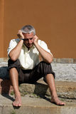 Worried businessman. Bare foot worried businessman sitting on steps with rolled up trousers Royalty Free Stock Image