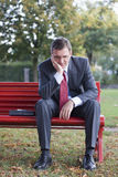 Worried businessman. Sitting on a red park bench Stock Photography