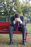 Worried businessman. Sitting on a red park bench Royalty Free Stock Photography