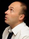 Worried businessman. Portrait of worried businessman in side profile, black background stock photo