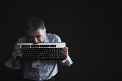 Worried Businessman Biting Computer Keyboard Royalty Free Stock Images