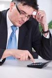 Worried businessman calculating Stock Photo